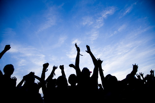 Photo of a happy waving crowd silhouetted against a blue sky.