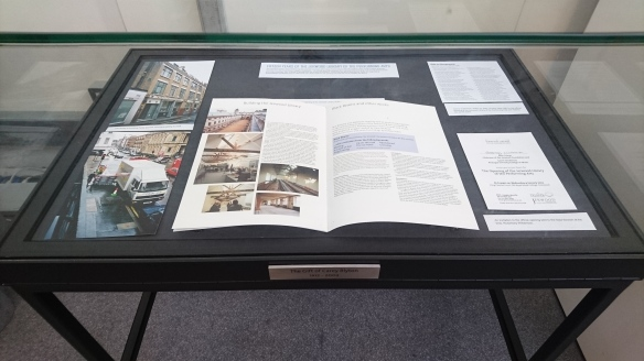 Display cabinet containing items related to the official opening of the Jerwood Library in 2002 (programme, invitiation, photos and a poem read at the event)