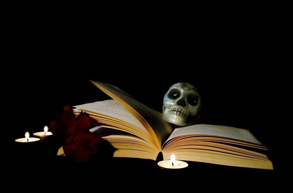 An book held open by a model skull, surrounded by candles